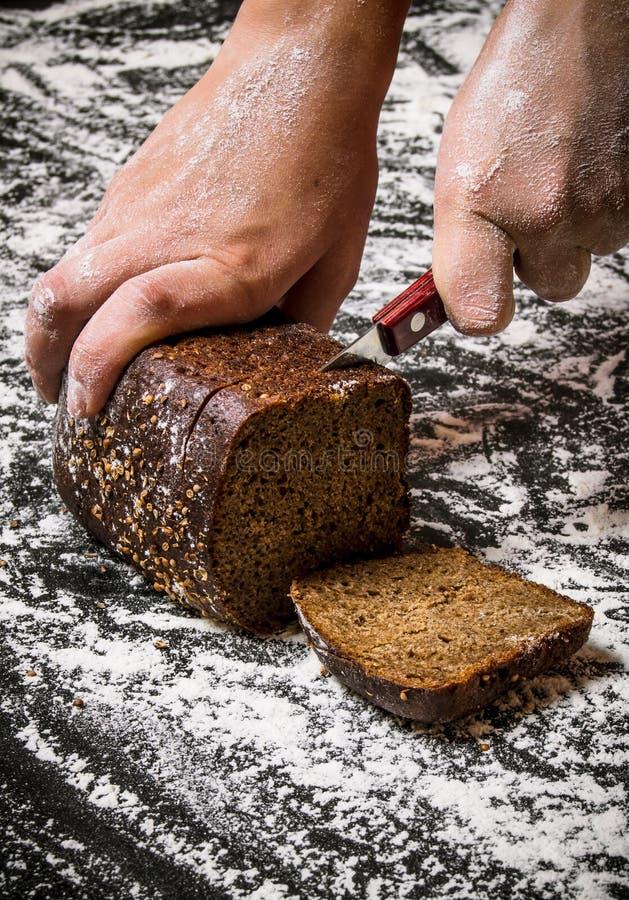 As mãos das mulheres recentemente cozidas cortadas do pão de centeio foto de stock