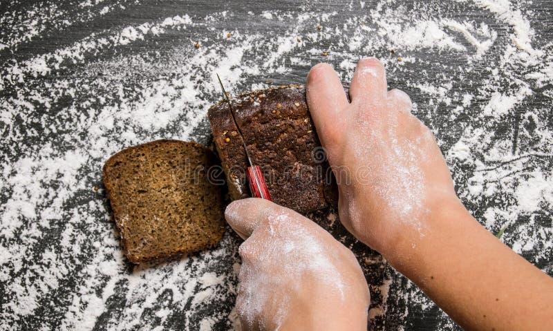 As mãos das mulheres recentemente cozidas cortadas do pão de centeio foto de stock royalty free