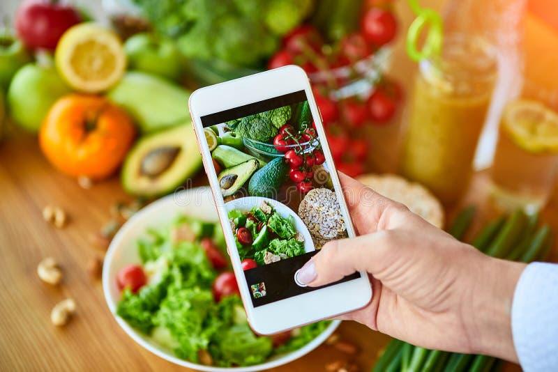As mãos das mulheres tiram fotos da salada de verduras com tomates e frutas Fotografia telefônica para as redes sociais ou imagens de stock