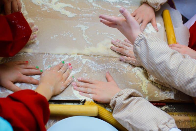 As mãos de cozinheiros das crianças espalharam a farinha na placa foto de stock royalty free