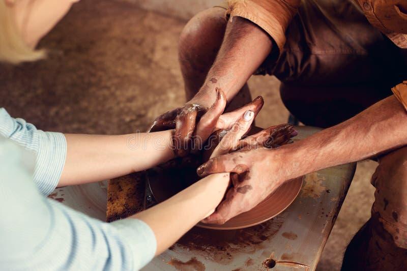 As mãos de dois povos criam o potenciômetro na roda do ` s do oleiro A cerâmica de ensino, ` s do carftman entrega o guiamento imagem de stock