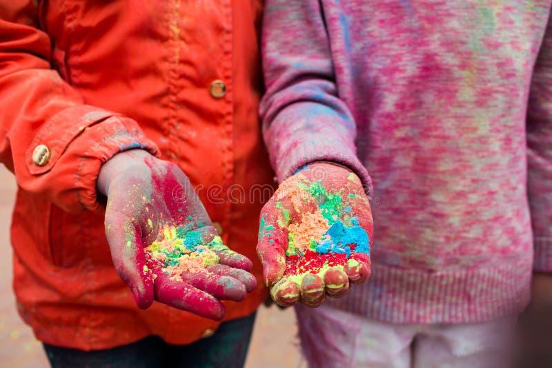 As mãos de jovens com as tinturas indianas em Holi colorem o festival imagens de stock royalty free