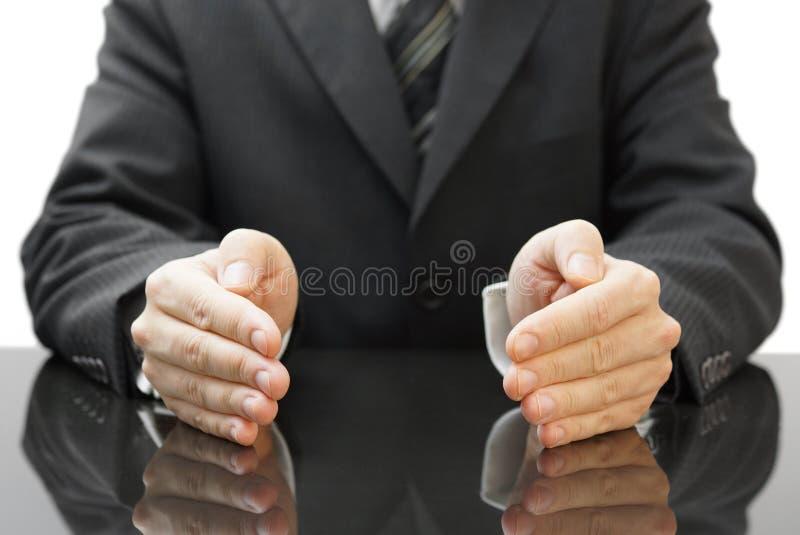 As mãos de proteção do homem de negócios fotografia de stock