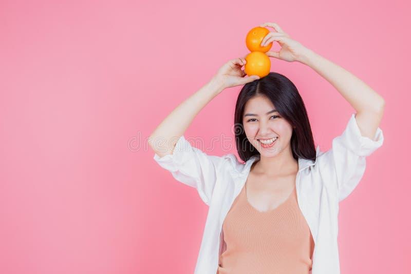 As mãos de sorriso alegres da mulher saudável guardam laranjas frescas imagens de stock