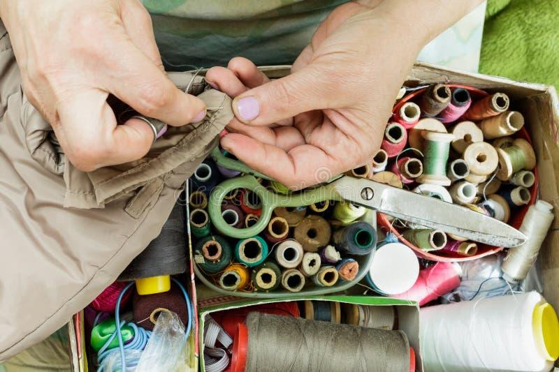 As mãos de trabalho de uma costureira com uma agulha, tesouras rosqueiam fotografia de stock
