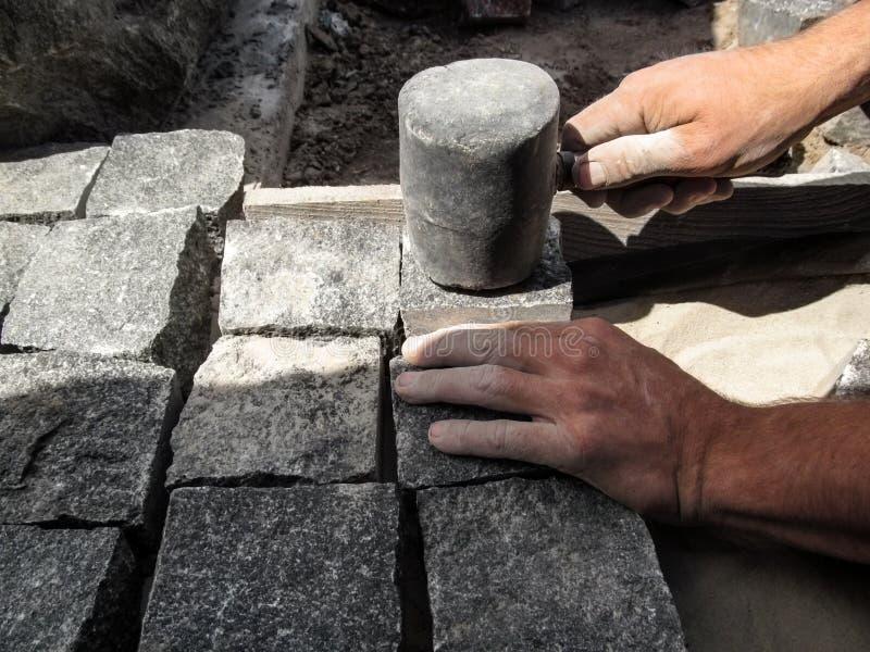 As mãos de trabalho do homem pavimentam pedras de pavimentação de um granito com um martelo de borracha grande preto fotografia de stock royalty free