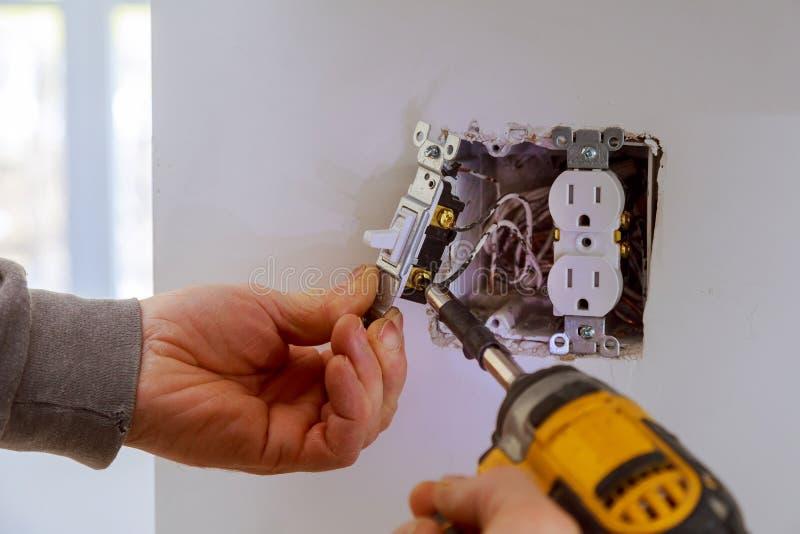 As mãos de um eletricista que instala um interruptor de alimentação imagem de stock