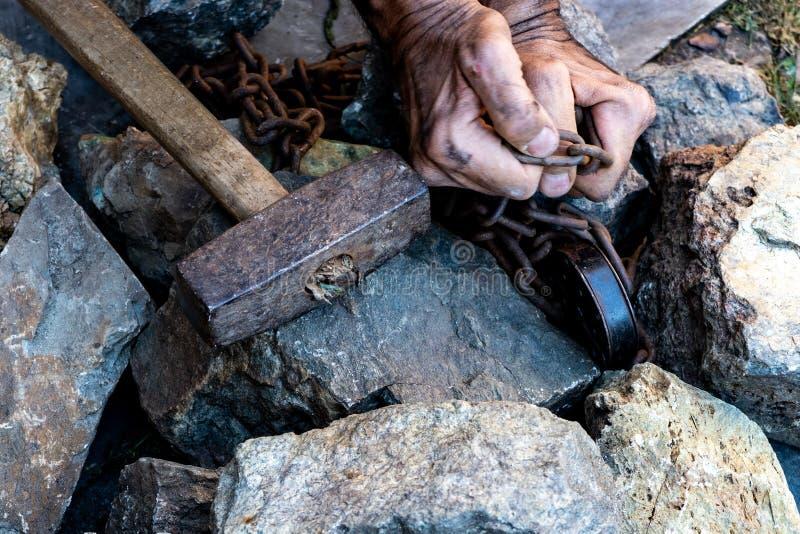As mãos de um escravo na tentativa de liberar-se O símbolo do trabalho de escravo M?os nas correntes fotos de stock royalty free