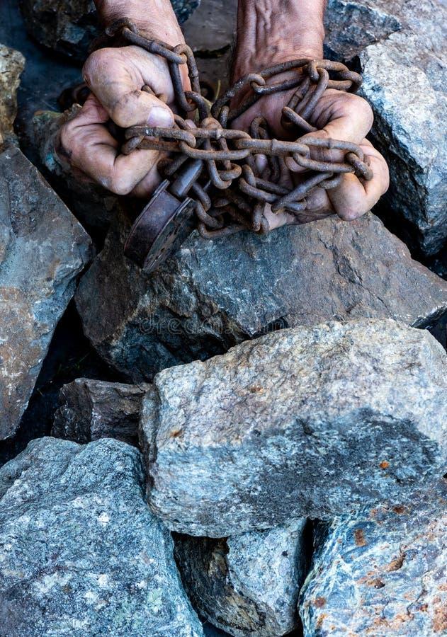 As mãos de um escravo na tentativa de liberar-se O símbolo do trabalho de escravo M?os nas correntes fotografia de stock royalty free