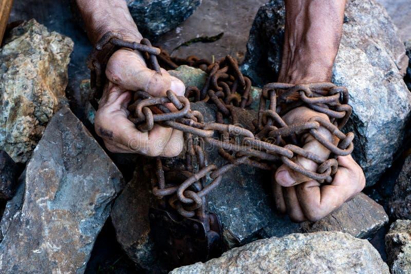 As mãos de um escravo na tentativa de liberar-se O símbolo do trabalho de escravo M?os nas correntes fotos de stock