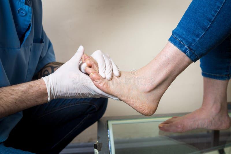 As mãos de um ortopedista do doutor do homem novo conduzem diagnósticos, teste do pé de pé de uma mulher, para a fabricação de in imagens de stock royalty free