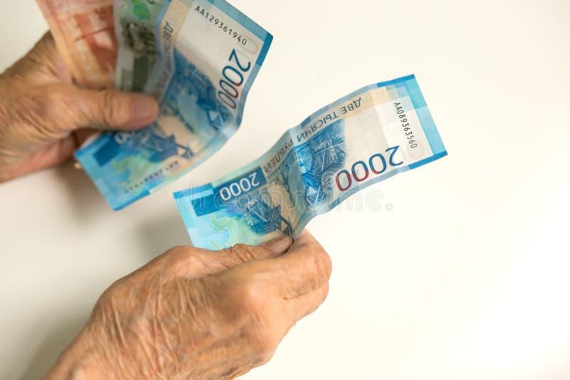 As mãos de um pensionista idoso consideram o dinheiro de um grande tamanho As mãos de um homem são velhas, decrépito imagem de stock royalty free