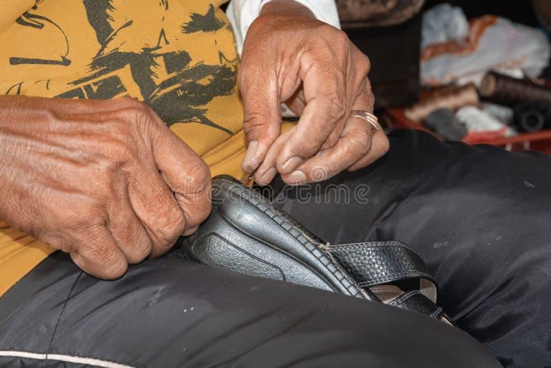 As mãos de um sapateiro costuram sandálias velhas na loja da rua imagens de stock royalty free