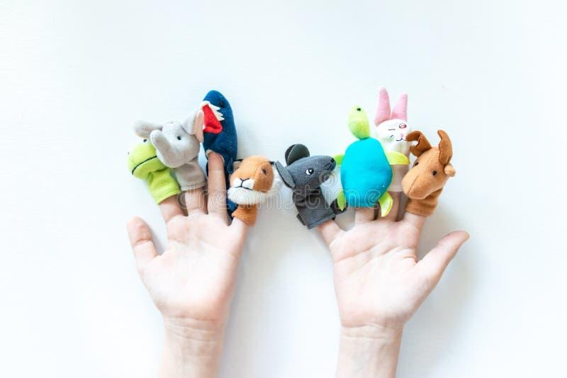 As mãos de uma criança com fantoches do dedo, brinquedos, bonecas fecham-se acima no fundo branco - jogar o teatro do fantoche e  fotografia de stock
