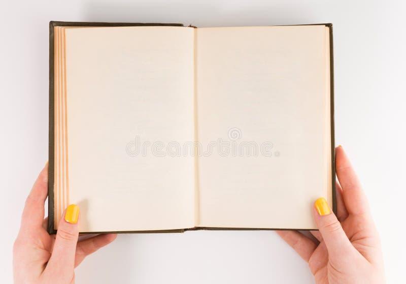 As mãos de uma fêmea dois da mulher mantêm uma propagação vazia vazia do livro isolada no branco fotografia de stock royalty free