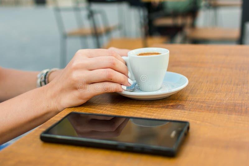 As mãos de uma jovem mulher estão guardando uma xícara de café em um terraço de um bar imagens de stock royalty free
