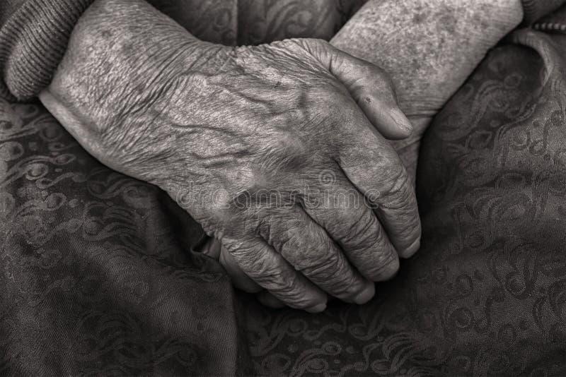 As mãos de uma mulher adulta dobraram-se em seu regaço, preto e branco foto de stock