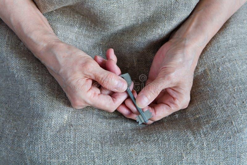 As mãos de uma mulher adulta para guardar a chave imagens de stock royalty free