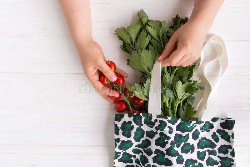 As mãos de uma mulher removem tomates orgânicos frescos do saco de compras de Eco com a cópia na moda do teste padrão do leopardo fotos de stock