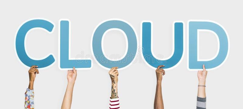 As mãos diversas que sustentam as letras azuis que formam a palavra nublam-se fotografia de stock royalty free