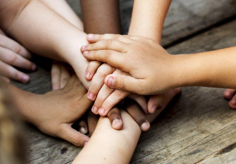 As mãos diversas são juntam-se junto na tabela de madeira fotografia de stock