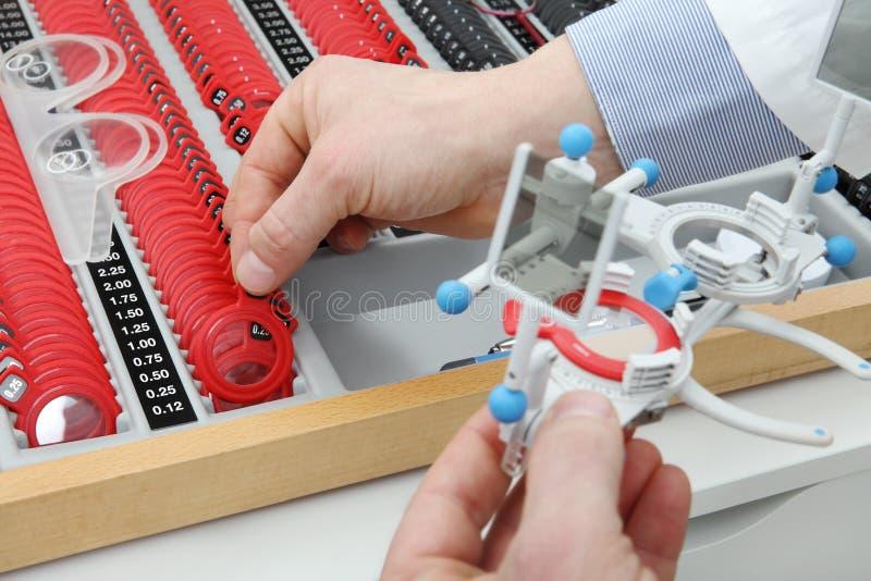 As mãos do ótico escolhem lentes, caixa experimental do quadro imagem de stock