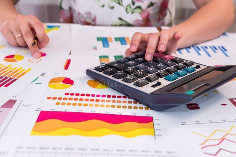As mãos do analista com gráficos de negócio, pena fotografia de stock royalty free