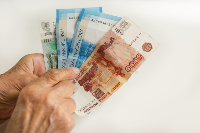 As mãos do ancião guardam cédulas em um valor nominal de 1,2,5 mil rublos Aposentado em Rússia fotografia de stock royalty free