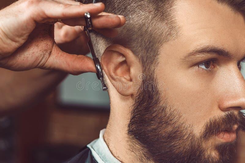 As mãos do barbeiro novo que fazem o corte de cabelo ao homem atrativo no barbeiro foto de stock royalty free