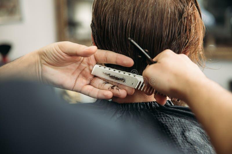 As mãos do barbeiro novo que fazem o corte de cabelo ao homem farpado atrativo no barbeiro fotografia de stock