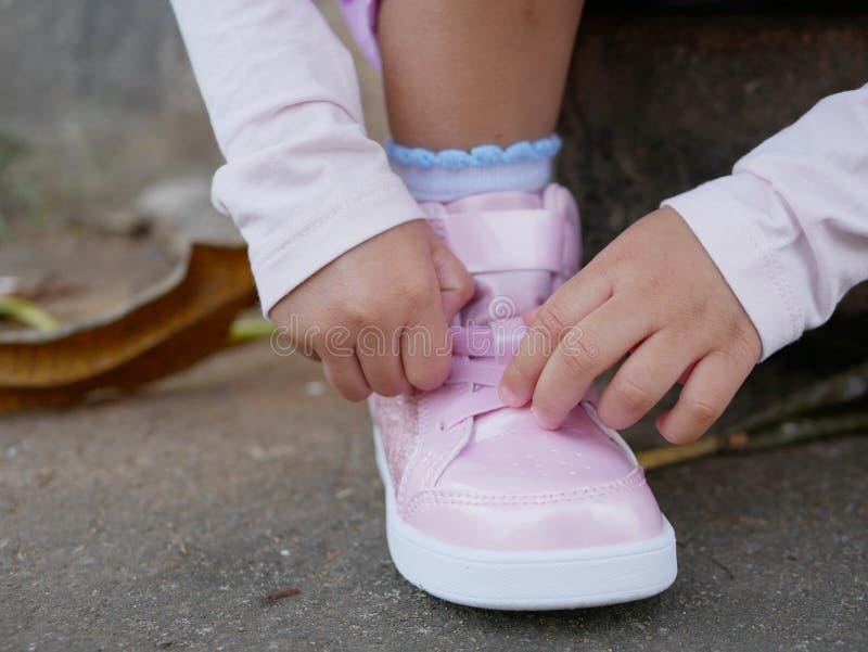 As mãos do bebê de Litlle que tentam atar só a sapata imagens de stock