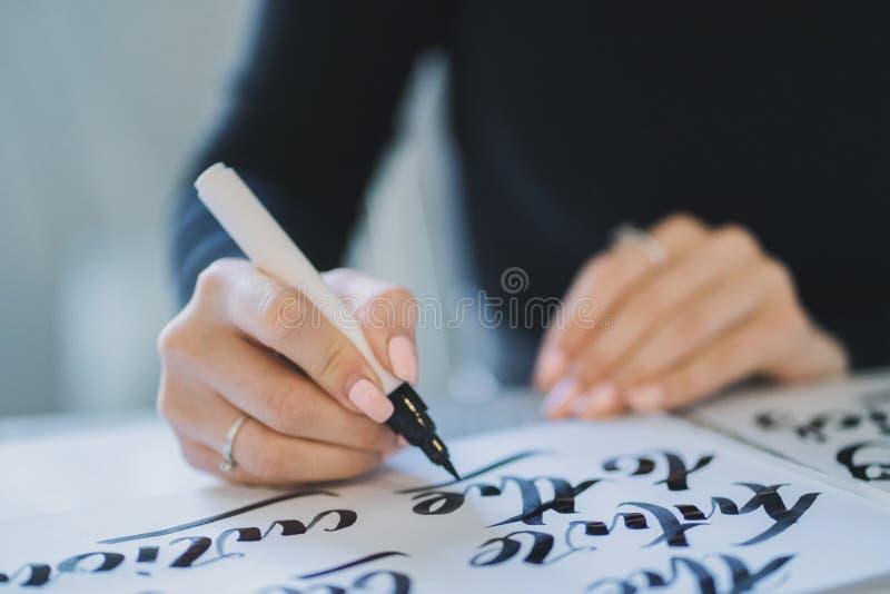 As mãos do calígrafo escrevem a frase no Livro Branco Inscreendo letras decoradas decorativas Caligrafia, projeto gráfico foto de stock