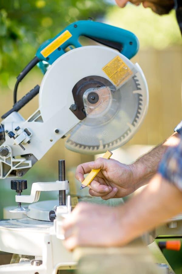 As mãos do carpinteiro que marcam na madeira na tabela consideraram imagem de stock royalty free