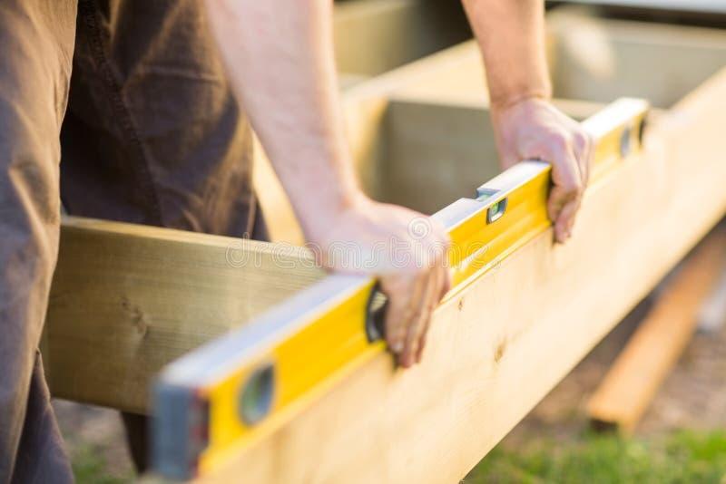 As mãos do carpinteiro que verificam ao nível da madeira no local imagens de stock royalty free