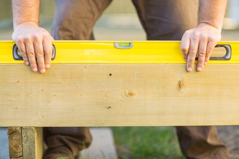 As mãos do carpinteiro usando o nível de espírito na madeira fotografia de stock royalty free
