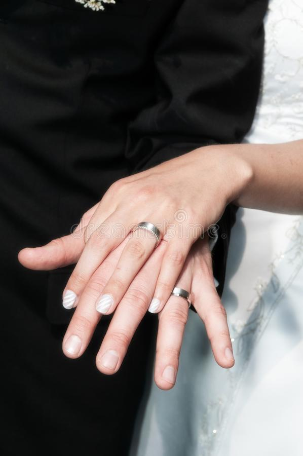 As mãos do casal que mostram as alianças de casamento imagem de stock royalty free