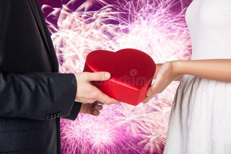 As mãos do close-up de pares novos com coração vermelho deram forma à caixa de presente imagens de stock royalty free