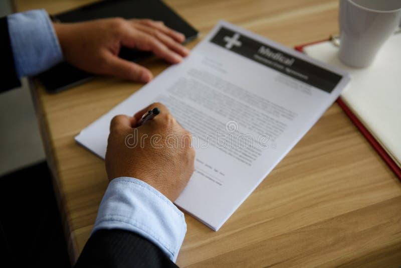 As mãos do close up do homem de negócios assinam o contrato imagens de stock