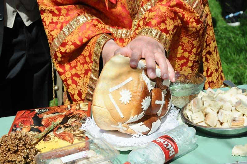 As mãos do corte do padre decoraram o pão foto de stock royalty free