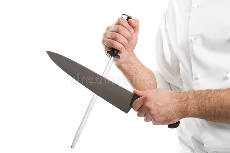 As mãos do cozinheiro chefe com faca sharpen o aço foto de stock royalty free