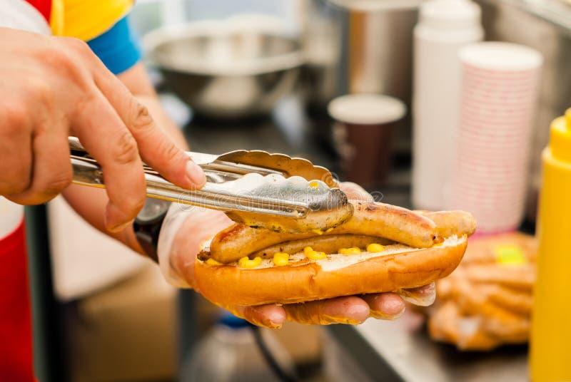 As mãos do cozinheiro chefe põem duas salsichas sobre um bolo foto de stock