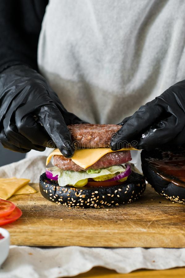 As mãos do cozinheiro chefe para cozinhar o hamburguer O conceito de cozinhar o cheeseburger preto Receita caseiro do Hamburger fotografia de stock
