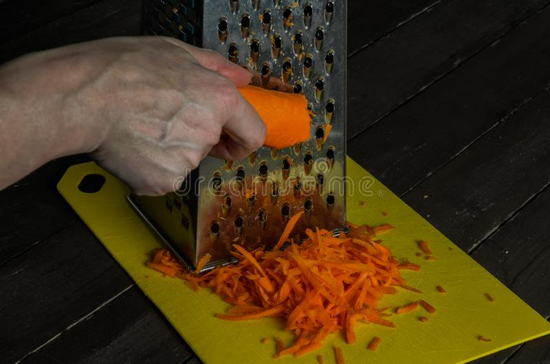 As mãos do cozinheiro rasparam cenouras imagens de stock royalty free