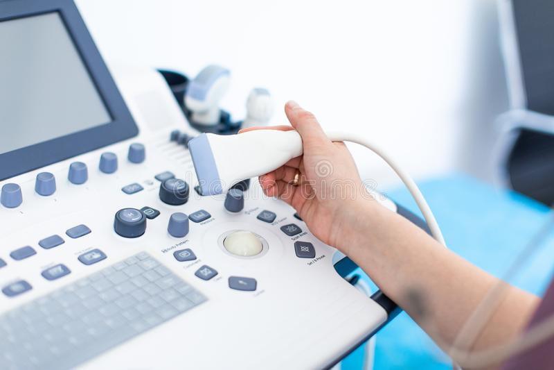 As mãos do doutor da mulher fecham-se acima com varredura do dispositivo do ultrassom imagem de stock