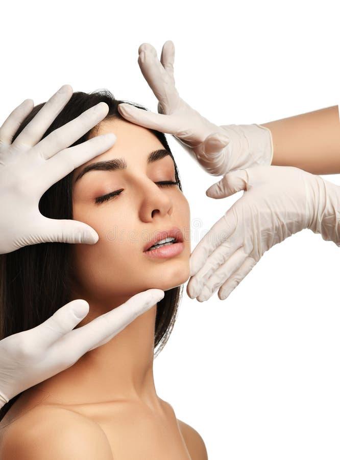 As mãos do doutor em luvas médicas tocam na cara bonita da jovem mulher com os olhos fechados após a cirurgia plástica imagem de stock royalty free