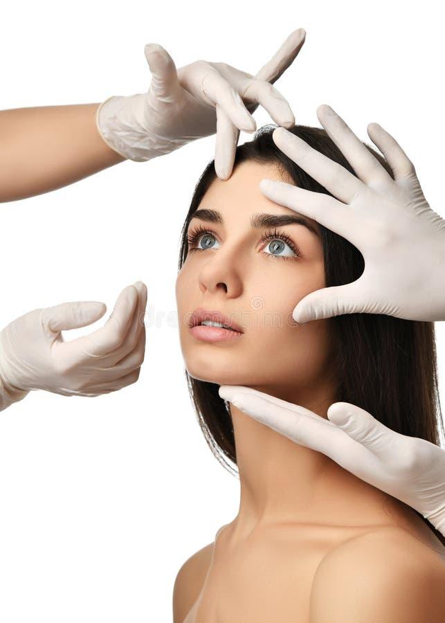 As mãos do doutor em luvas médicas tocam na cara bonita da jovem mulher com os olhos fechados após a cirurgia plástica foto de stock royalty free