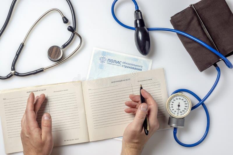 As mãos do doutor escrevem o relatório médico no informe médico do paciente foto de stock royalty free