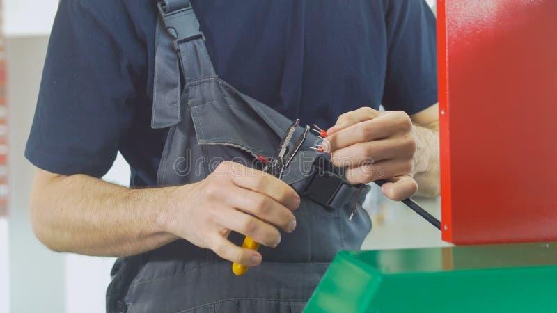 As mãos do eletricista funcionam com fios bondes foto de stock