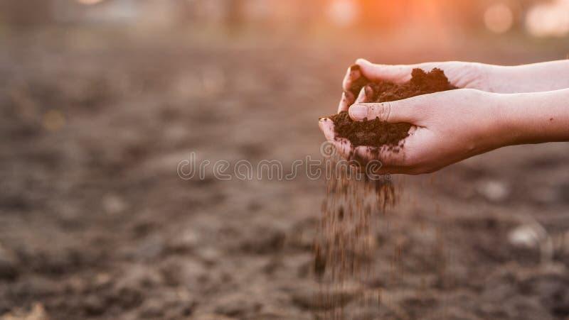 As m?os do esmagamento do fazendeiro com derramam para fora o solo sobre o campo Trabalho da mola imagens de stock royalty free
