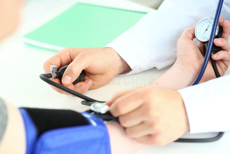 As mãos do especialista que guardam o tonometer fotografia de stock